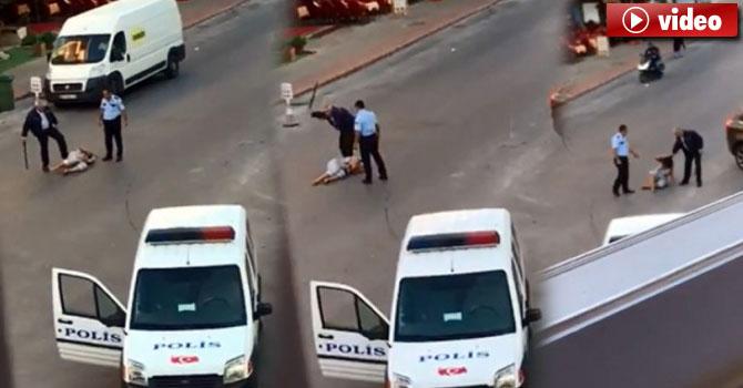 Polisler yerdeki kadına copla vurup, tekmeledi